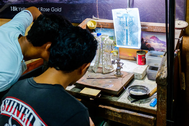 Workers creating a piece of silver art