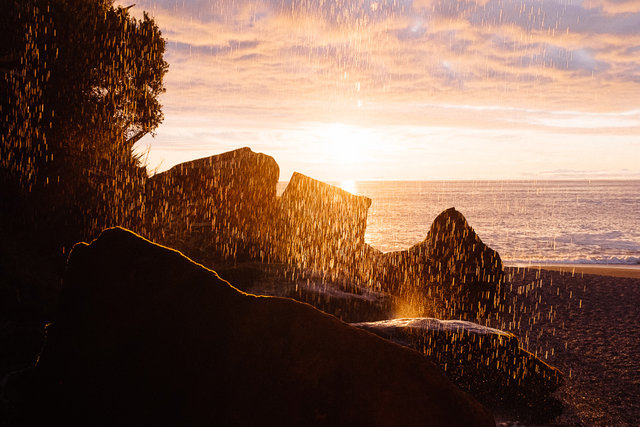 A stunning sunset through a small waterfall near Punakaiki